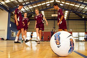 student playing football indoor